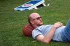 Jerry resting on a basketball in between Cornhole games in the backyard.