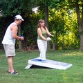 Wes and Abby laughing while playing a game of Cornhole.
